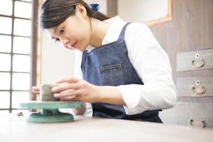陶芸教室で粘土を触っている女性の写真素材 [FYI02664288]