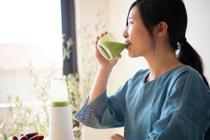 グリーンスムージーを飲んでいる女性の写真素材 [FYI02664299]