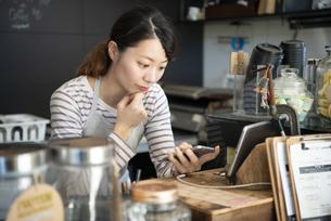 カフェのカウンターでスマホを見ている女性店員の写真素材 [FYI02664302]