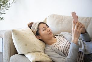 ソファに寝転んでスマホを見ている女性の写真素材 [FYI02664312]