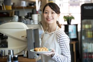 パンを持って笑っている店員の女性の写真素材 [FYI02664323]