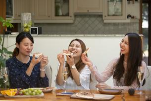 ホームパーティでピザを食べている女性たちの写真素材 [FYI02664324]