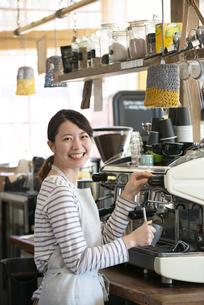 笑顔でエスプレッソマシンを触っている店員の女性の写真素材 [FYI02664332]