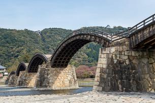山の上の岩国城を遠くに見る錦帯橋の写真素材 [FYI02664353]