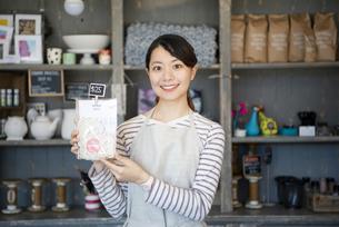 商品を持っている笑顔の女性店員の写真素材 [FYI02664374]