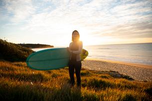 サーフボードを抱えてビーチに立っている女性の写真素材 [FYI02664375]