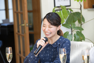 家でカラオケパーティをしている女性の写真素材 [FYI02664411]