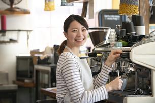 笑顔でエスプレッソマシンを触っている店員の女性の写真素材 [FYI02664412]