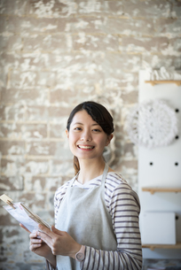 商品を持っている笑顔の女性店員の写真素材 [FYI02664425]