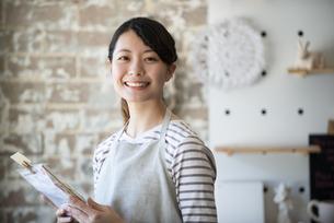 商品を持っている笑顔の女性店員の写真素材 [FYI02664453]