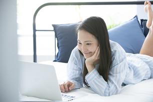 ベッドの上でパソコンを触っているパジャマ姿の女性の写真素材 [FYI02664467]