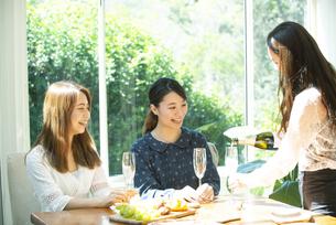 ホームパーティを笑顔で楽しんでいる女性3人の写真素材 [FYI02664477]