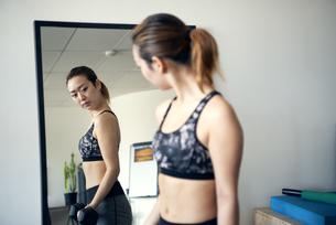 ジムで鏡を見ながら筋トレをしている女性の写真素材 [FYI02664486]