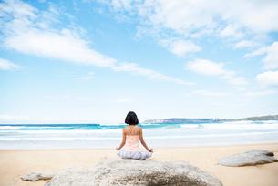 ビーチでヨガをしている女性の写真素材 [FYI02664530]