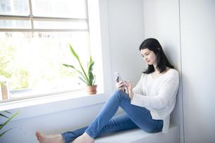 窓辺に座ってスマホを触っている女性の写真素材 [FYI02664535]