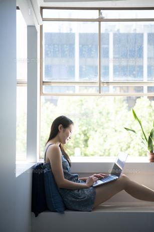 窓辺に座ってパソコンを触っている女性の写真素材 [FYI02664543]