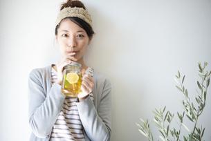 アイスレモンティーを紙ストローで飲んでいる女性の写真素材 [FYI02664544]