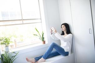 窓辺に座ってスマホを触っている女性の写真素材 [FYI02664545]
