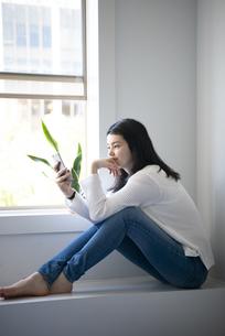 窓辺に座ってスマホを触っている女性の写真素材 [FYI02664549]