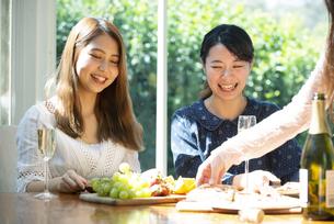 ホームパーティを笑顔で楽しんでいる女性3人の写真素材 [FYI02664559]