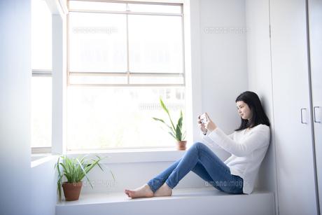 窓辺に座ってスマホを触っている女性の写真素材 [FYI02664561]