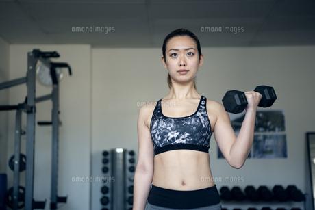 ジムでダンベルを使って筋トレをしている女性の写真素材 [FYI02664583]