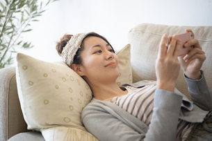 ソファに寝転んでスマホを見ている女性の写真素材 [FYI02664596]