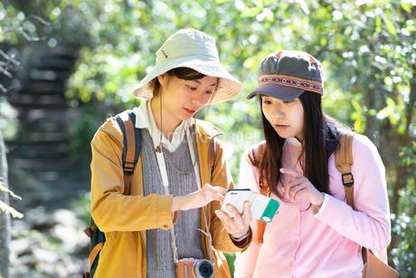 ハイキング中にスマホで地図を見ている女性2人の写真素材 [FYI02664608]