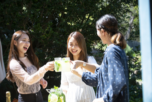 ガーデンパーティで乾杯をしている笑顔の女性3人の写真素材 [FYI02664621]