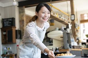 笑顔で接客をしている店員の女性の写真素材 [FYI02664642]