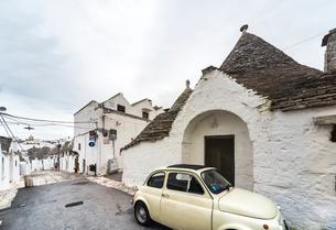 駐車中の可愛い車を見るトゥルッリの町並みの写真素材 [FYI02664715]