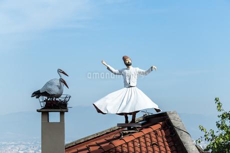 メヴラーナ人形とツガイのコウノトリのオブジェを空に見上げるの写真素材 [FYI02664722]