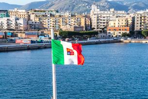パレルモの街並みを背景に風に靡くイタリア共和国の商船旗の写真素材 [FYI02664762]