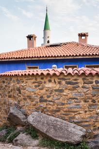 味わいある塀と伝統様式家屋の瓦屋根越しに見るモスクのミナレットの写真素材 [FYI02665682]