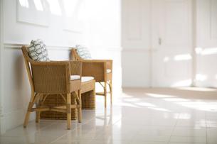 陽射しの入る白い部屋にある藤の椅子の写真素材 [FYI02666057]