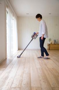 リビングで掃除機をかける女性の写真素材 [FYI02666092]