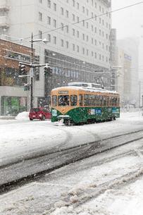 大雪の中 富山駅前を走る路面電車の写真素材 [FYI02666156]