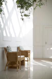 陽射しの入る白い部屋にある藤の椅子の写真素材 [FYI02666340]
