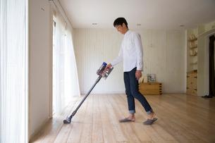 リビングで掃除機をかける男性の写真素材 [FYI02666523]