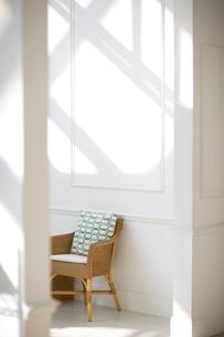 陽射しの入る白い部屋にある藤の椅子の写真素材 [FYI02666570]