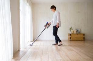 リビングで掃除機をかける女性の写真素材 [FYI02666572]