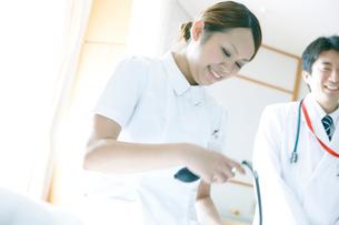 ベッドサイドで血圧を測る看護師の写真素材 [FYI02666603]