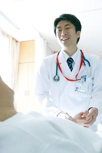 ベッドサイドで患者を回診する医師の写真素材 [FYI02666612]