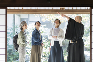 寺院を案内する住職と3人の女性の写真素材 [FYI02666629]