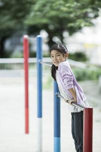 鉄棒で遊ぶ女の子の写真素材 [FYI02666647]