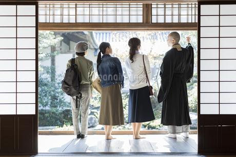 寺院を案内する住職と3人の女性の写真素材 [FYI02666661]