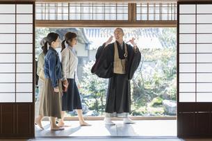 寺院を案内する住職と3人の女性の写真素材 [FYI02666729]