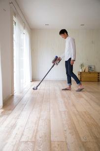 リビングで掃除機をかける男性の写真素材 [FYI02666741]
