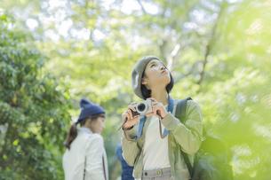 カメラを持って見上げる若い女性の写真素材 [FYI02666814]