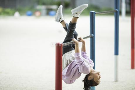 鉄棒で遊ぶ女の子の写真素材 [FYI02666825]